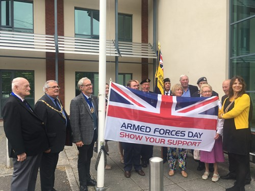 Councillors Les Cruwys and Colin Slade with members of the armed forces raising the flag on Armed Forces Day