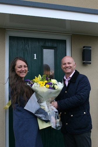 Image of new tenant Miss Pavanello accepting a bouquet of flowers from Mid Devon District Council's Director of Operations, Andrew Pritchard